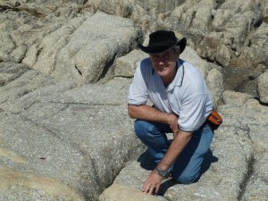 Tas Walker, inspecting granite outcrop, says Castle Hill is much younger than generally believed.