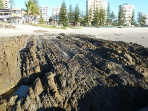 Figure 2. Example of the Neranleigh Fernvale Beds exposed on Rainbow Beach, near Snapper Rock at Coolangatta, Australia. These thick and thin beds have been tilted vertically, faulted such that they do not line up, and shaved off at the top.