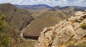 Ormiston Gorge, from the western rim, changes direction through the hard quartzite strata. Mount Giles, the tallest mountain in the Northern Territory, is centre background. Exposed and fractured quartzite rock is visible in the foreground. (Image courtesy of Tourism NT.)