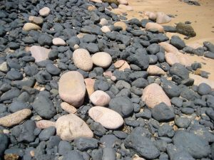 Boulders of black basalt and pink granite on beach